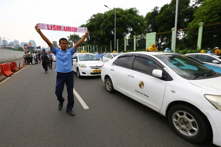 Conventional taxi drivers stage a rally against the ride-hailing services in front of the Merdeka Palace in Jakarta on March 14, 2016.