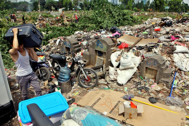 A resident of Menteng Pulo Cemetery collects his belonging after he was evicted in April 2016. Over 250 illegal buildings, which were built on graves, were demolished.