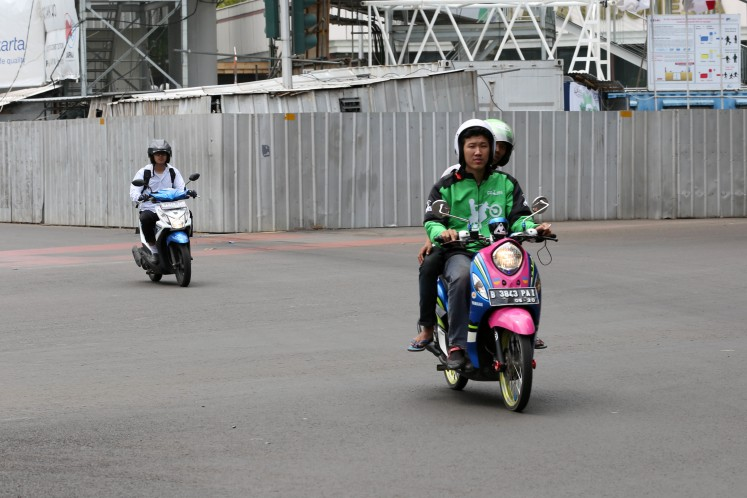 A driver from popular ride-hailing application Go-Jek transports a passenger to their destination on Dec. 18, 2015.