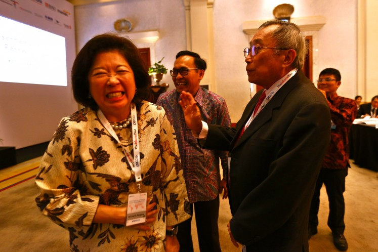 Mari Elka Pangestu (left) laughs with the publisher of The Jakarta Post Jusuf Wanandi (right) on the sidelines of a seminar held by The Jakarta Post to celebrate its 33rd anniversary in April 2016.