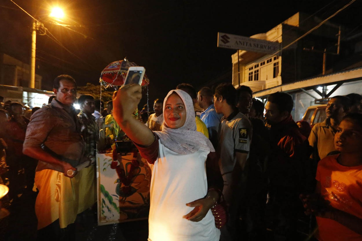 A Muslim resident takes a selfie in front of the statue of the god Murugan before the Panguni Uthiram procession. JP/Hotli Simanjuntak