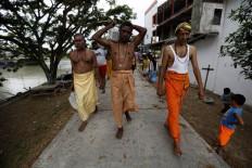 A Hindu priest leads followers to the location of the Panguni Uthiram ritual by the riverside. JP/ Hotli Simanjuntak