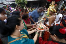Devotees present offerings to the statue of Lord Murugan in front of the temple at the end of the Panguni Unthiram parade. JP/ Hotli Simanjuntak