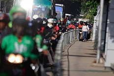 Alfini walks on the sidewalk at Jalan Sudirman Jakarta while a group of motorcycles attempting to avoid traffic by trespassing on a sidewalk on Monday. She took action to protest unruly bikers. The Jakarta Post/ Dhoni Setiawan