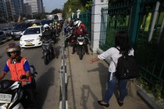 A rider gvies a thumb for Alfini action. She daringly blocks a group of motorcycles attempting to avoid traffic by trespassing on a sidewalk on Jl Sudirman in Jakarta on Monday. She took action to protest unruly bikers. The Jakarta Post/ Dhoni Setiawan