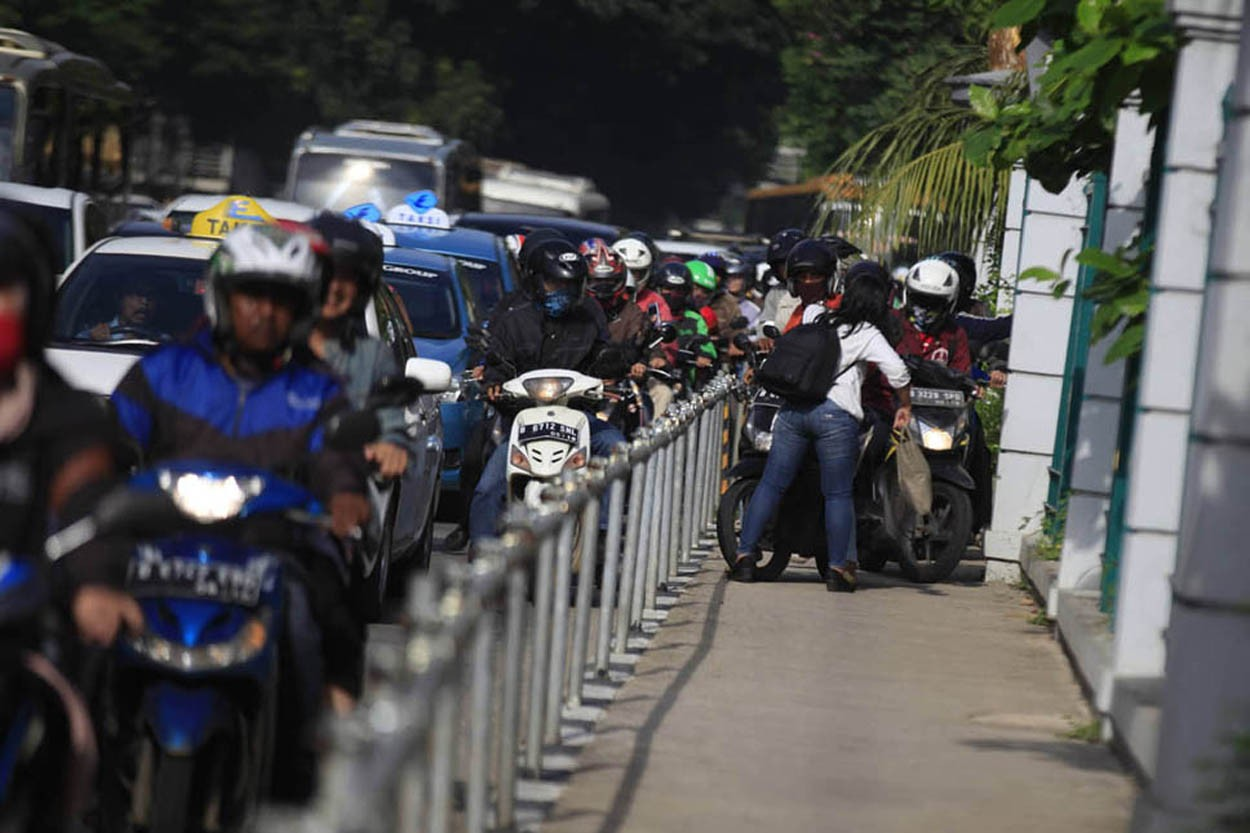 Alfini asks a group of motorcycles attempting to avoid traffic by trespassing on a sidewalk to turn back at Jalan Sudirman Jakarta on Monday. She took action to protest unruly bikers. The Jakarta Post/ Dhoni Setiawan