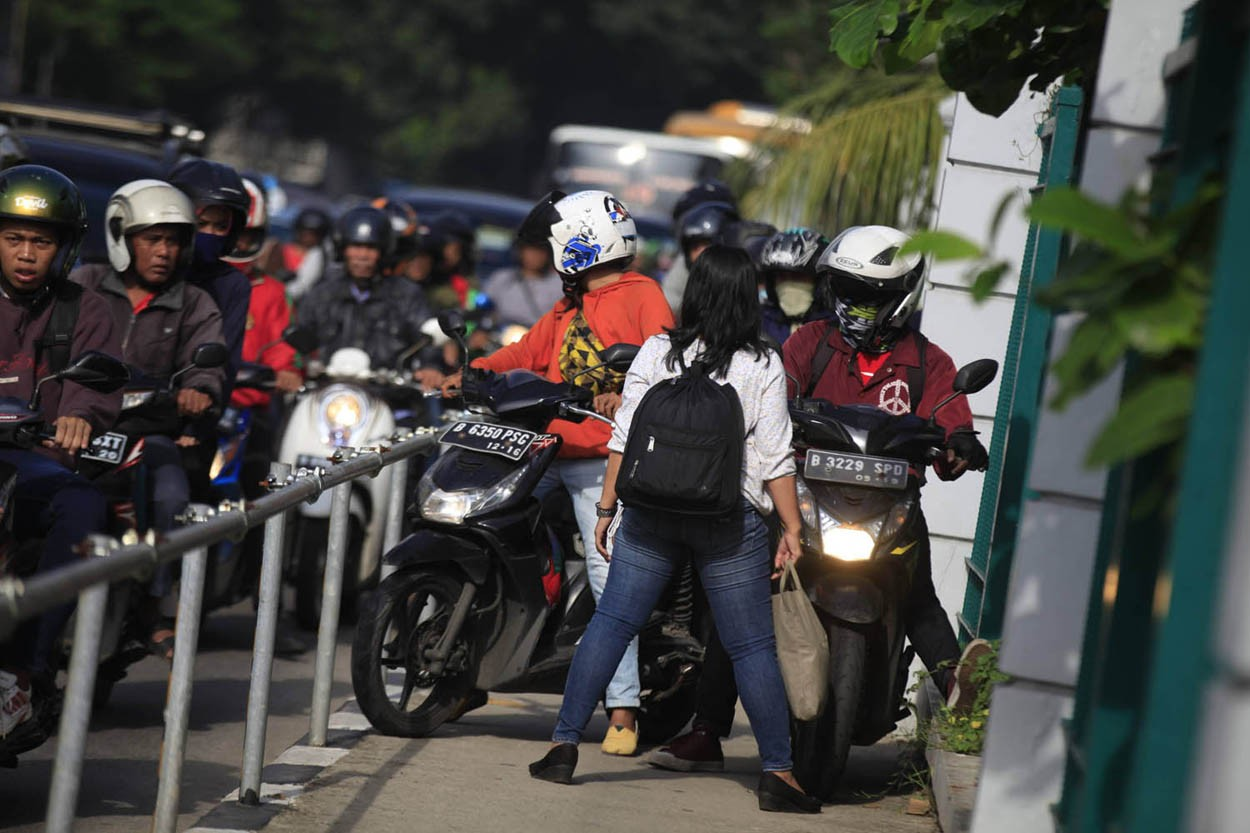 Alfini daringly blocks a group of motorcycles attempting to avoid traffic by trespassing on a sidewalk on Jl Sudirman in Jakarta on Monday. She took action to protest unruly bikers. The Jakarta Post/ Dhoni Setiawan