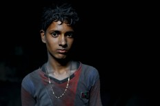 In this Sunday, June 12, 2016, photo, Nizam, 11, looks towards camera as he works at a factory that makes metal utensils in Dhaka, Bangladesh, Sunday, June 12, 2016. He earns less than $5 per week. AP Photo/ A.M. Ahad