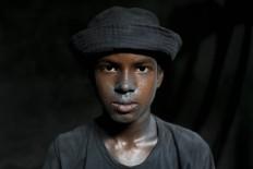 Bangladeshi boy Imran, 11, looks towards camera as he works at a factory that makes metal utensils in Dhaka, Bangladesh, Sunday, June 12, 2016. He earns less than $5 per week. AP Photo/ A.M. Ahad