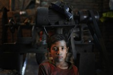 Bangladeshi boy Robin,10, looks towards camera as he works at a factory that makes metal utensils in Dhaka, Bangladesh, Sunday, June 12, 2016. He earns less than $5 per week. AP Photo/ A.M. Ahad