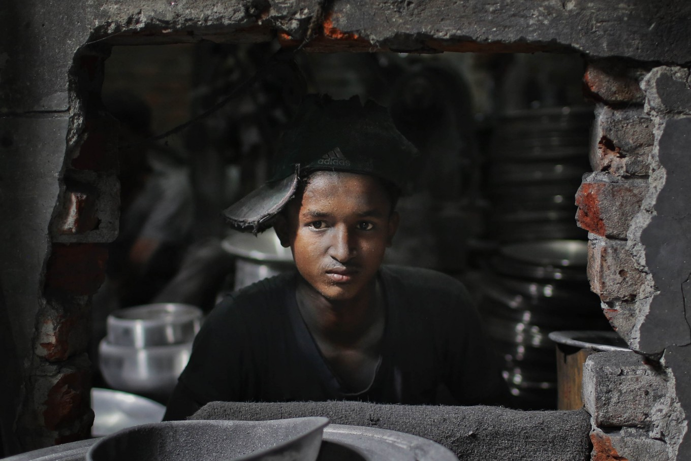 Bangladeshi boy Rubel, 12, looks towards camera as he works at a factory that makes metal utensils in Dhaka, Bangladesh, Sunday, June 12, 2016. He earns less than $5 per week. AP Photo/ A.M. Ahad