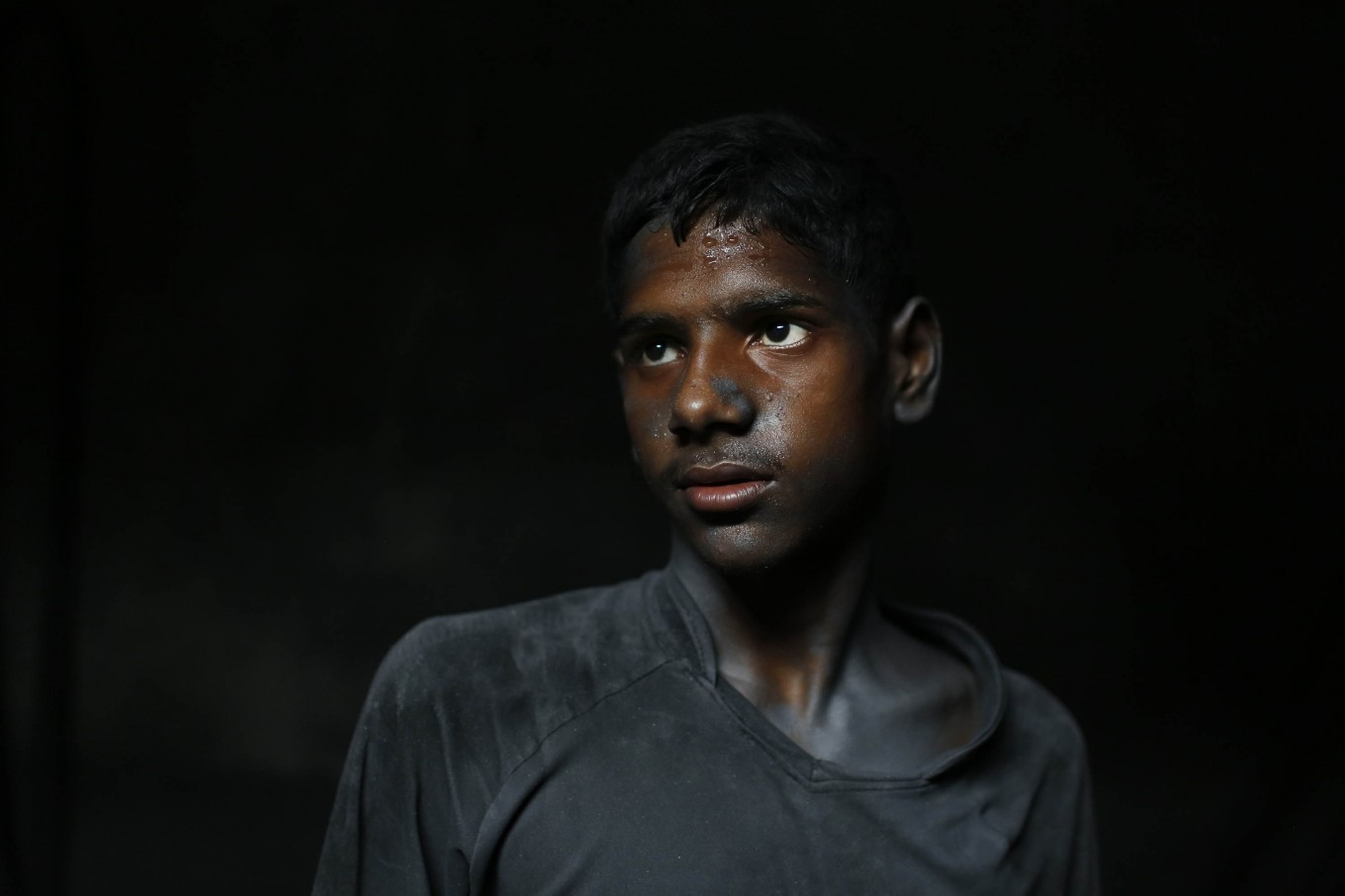 In this Sunday, June 12, 2016, photo, Ridoy, 11, poses for a portrait as he works at a factory that makes metal utensils in 