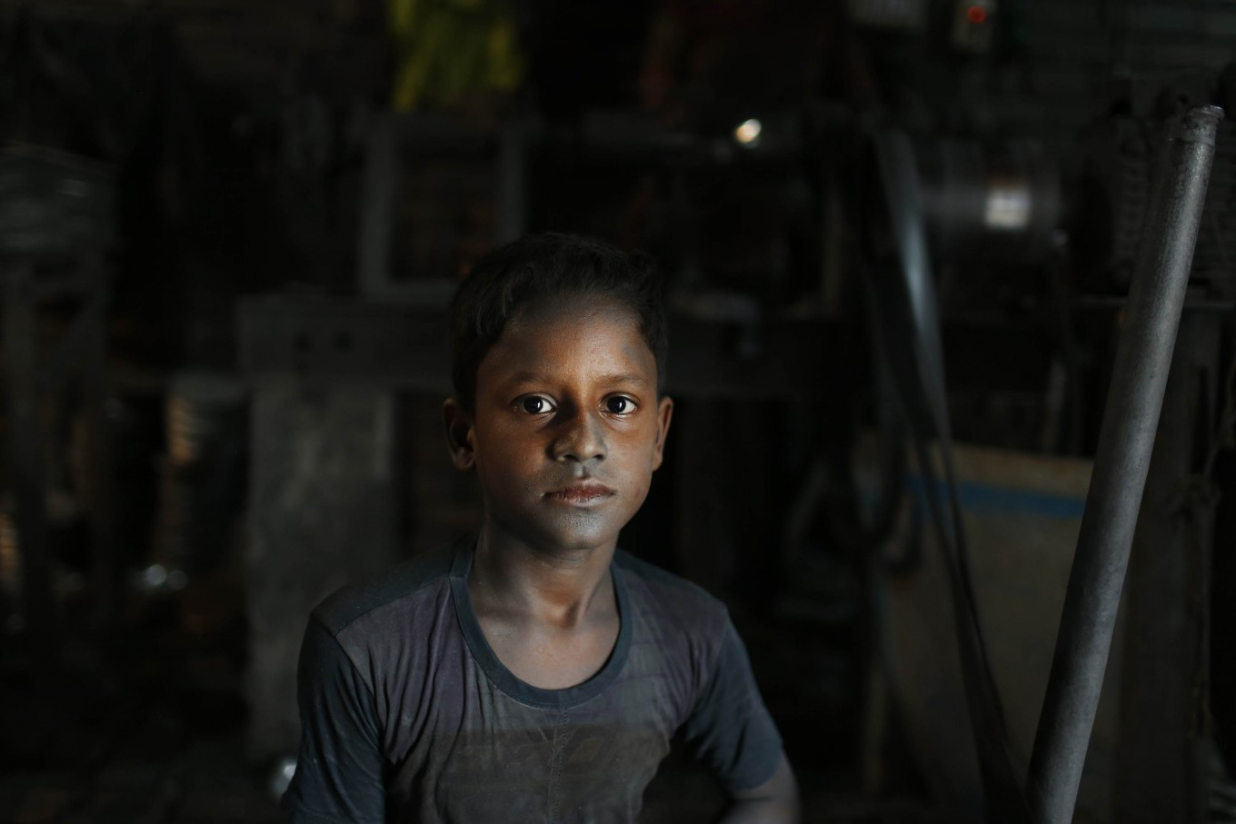 In this Sunday, June 12, 2016, photo, Bangladeshi child Arif, 9, looks towards camera as he works at a factory that makes metal utensils in Dhaka, Bangladesh. AP Photo/ A.M. Ahad