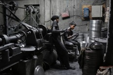 In this Sunday, June 12, 2016, photo, boys Imran, 11, left, and Nizam, 11, look at a mobile phone, as they take a break during their work at a factory that makes metal utensils in Dhaka, Bangladesh. AP Photo/ A.M. Ahad
