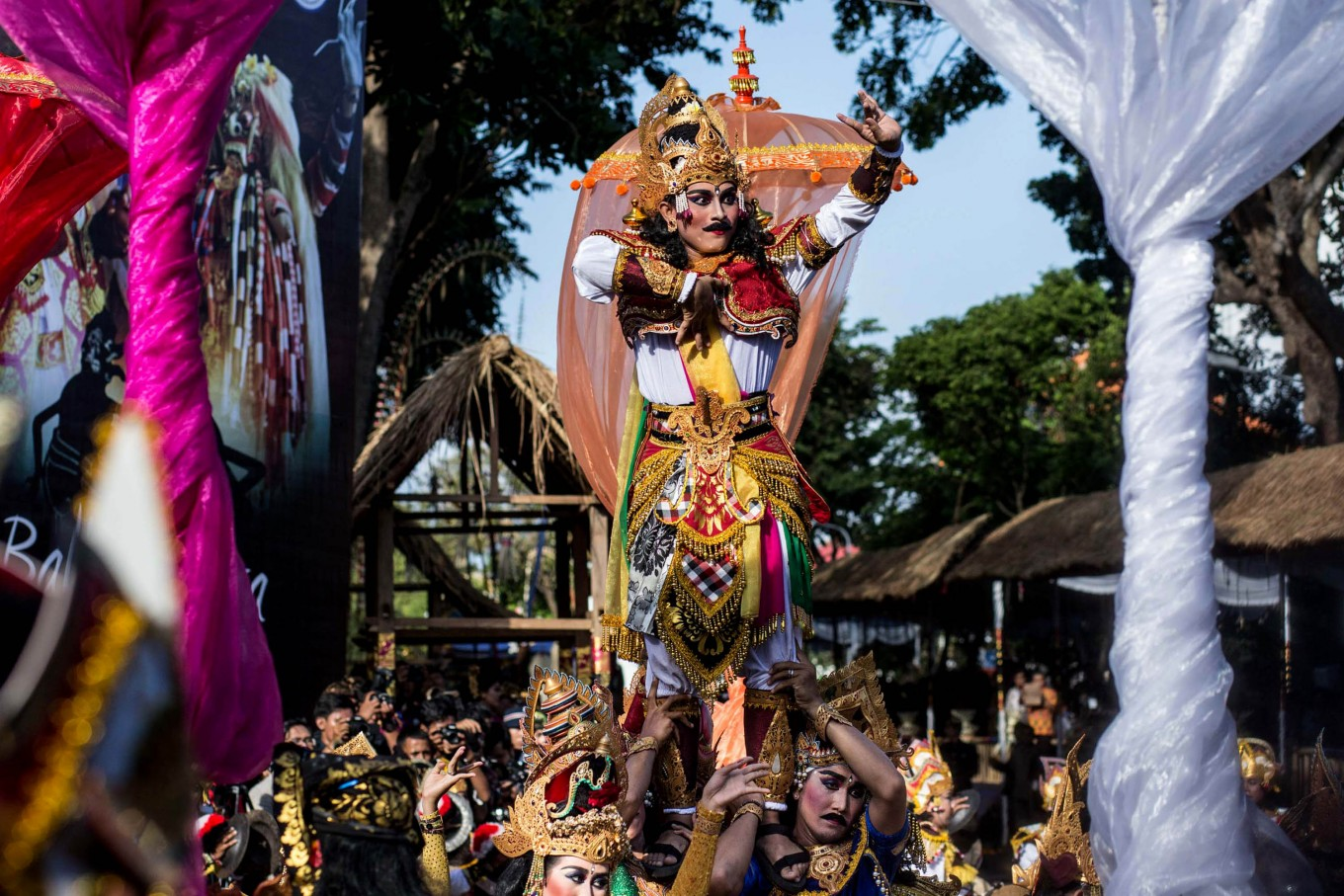 A Balinese dancer stands on the shoulders of other dancers during the street parade.  JP/Agung Parameswara