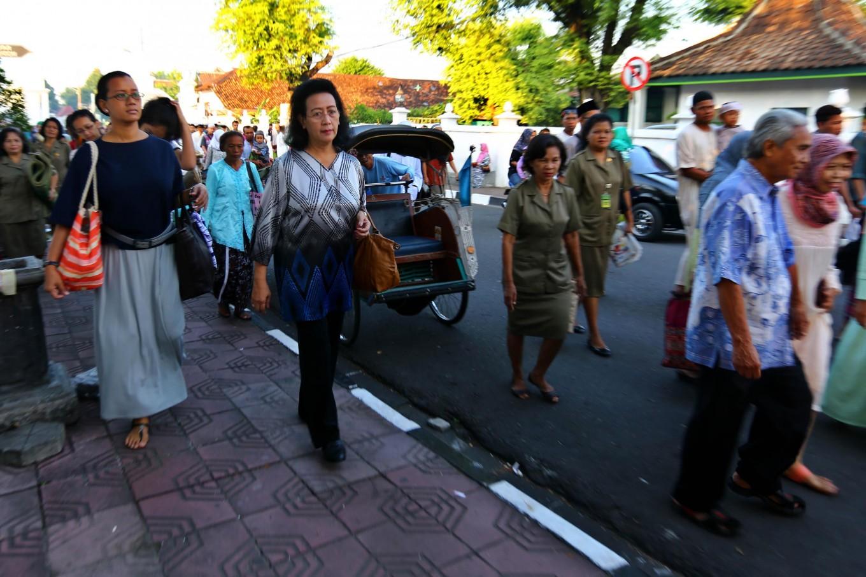 Queen Hemas of the Yogyakarta Kingdom [on sidewalk, right], accompanied by her daughter Princess Mangkubumi, walks to Alun Alun Utara [North square] of Yogyakarta to join Idul Fitri prayers with other common folk. JP/ Wienda Parwitasari
