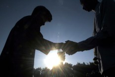 Two men shake hands after Idul Fitri prayers at Sudirman Square, Denpasar, Bali, on Wednesday. Millions of Muslims in Indonesia celebrate the festivities by asking for people's forgiveness after 30 days of dawn-to-dusk fasting during Ramadhan this year. JP/ Zul Trio Anggono