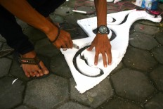 Tono cuts styrofoam to decorate his pedal car before the pedal cars carnival at the South Square in Panembahan during the Alun Alun Selatan Festival. JP/ Aditya Sagita