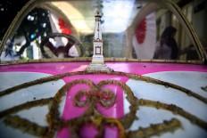 A miniature of Tugu, Yogyakarta's iconic monument, is put on a pink pedal car for the carnival. JP/ Aditya Sagita