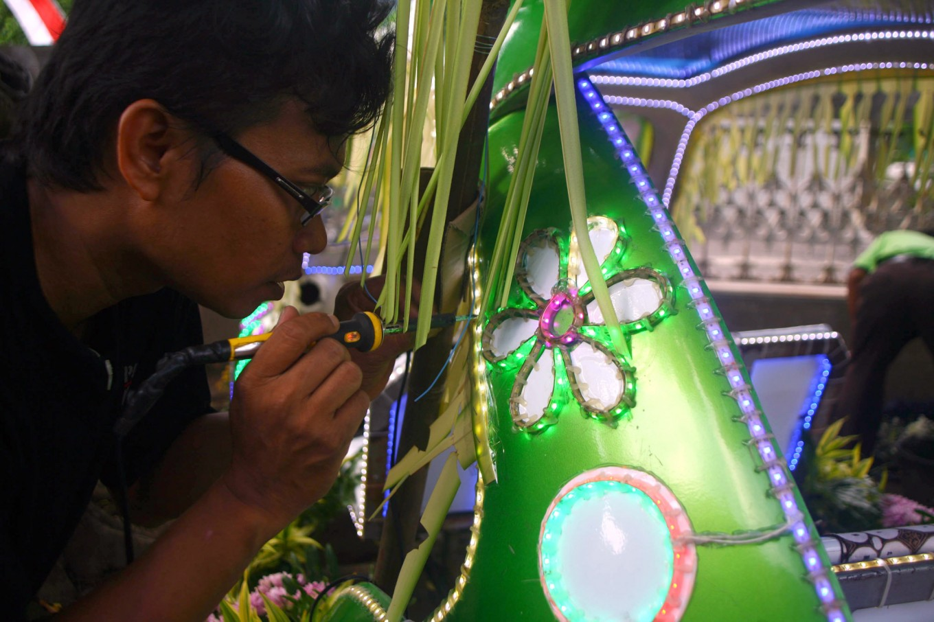 Aan works on lighting decoration on the body of the car for the carnival. JP/ Aditya Sagita