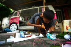 Seno prepares light decorations for a pedal car before the carnival. JP/ Aditya Sagita
