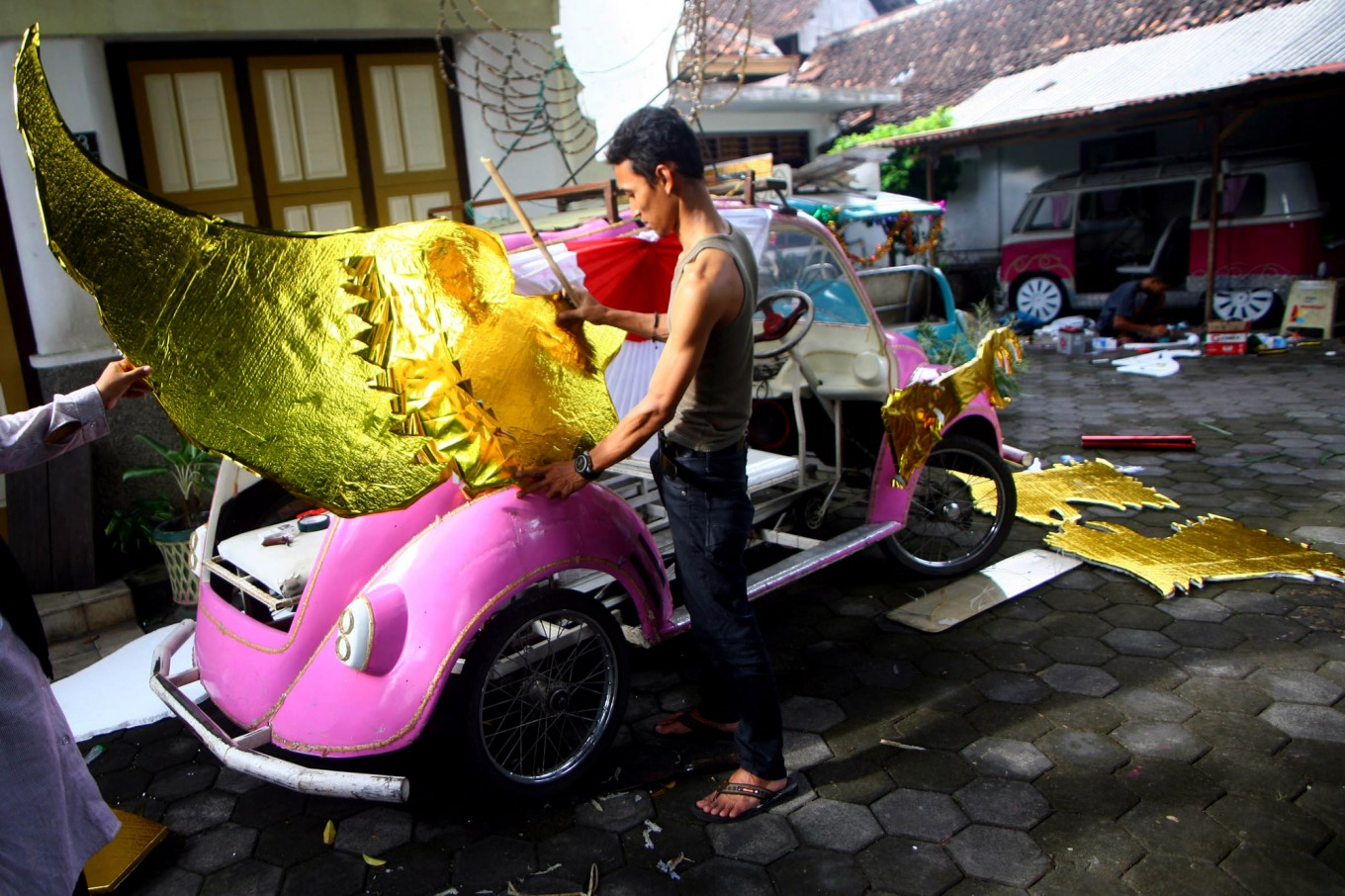 Tono and his wife make decorations for their pedal car for the carnival on Aug. 13. JP/ Aditya Sagita