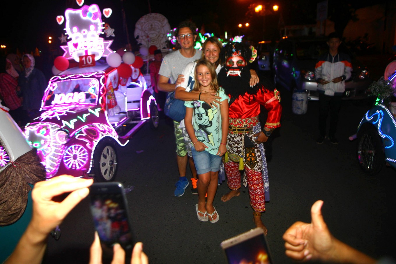 A family of foreign tourists pose with a man dressed as a wayang character during the festival. JP/ Aditya Sagita
