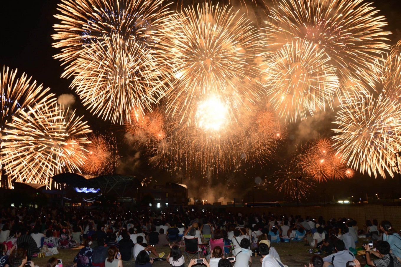 People sit on mats on the edge of Biwa Lake to enjoy fireworks. JP/Tarko Sudiarno