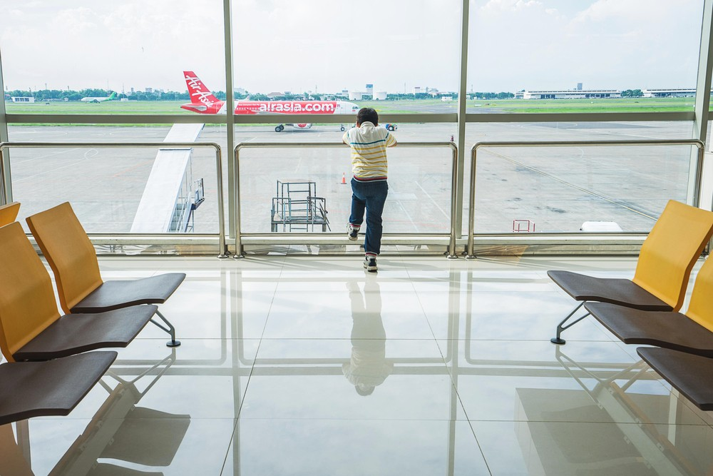 A boy looks at an AirAsia plane that is preparing for take-off at an airport terminal in Surabaya, East Java, on June 22, 2016. Image: Shutterstock.com/dreamstory