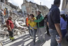 A woman is comforted as she walks through rubble after an earthquake, in Amatrice, central Italy, Wednesday, Aug. 24, 2016. A devastating earthquake rocked central Italy early Wednesday, collapsing homes on top of residents as they slept. At least 23 people were reported dead in three hard-hit towns where rescue crews raced to dig survivors out of the rubble, but the toll was expected to rise as crews reached homes in more remote hamlets. AP Photo/Alessandra Tarantino