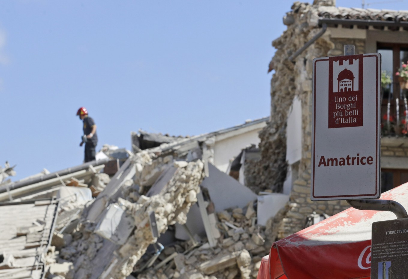 """Rescuers work in Amatrice, central Italy, Wednesday, Aug. 24, 2016, where a magnitude 6 quake struck at 3:36 a.m. [0136 GMT] and was felt across a broad swath of central Italy, including Rome where residents of the capital felt a long swaying followed by aftershocks. Turistic sign at right reads in Italian : """"Amatrice, one of the most beautiful hamlets in Italy"""". AP Photo/Alessandra Tarantino"""