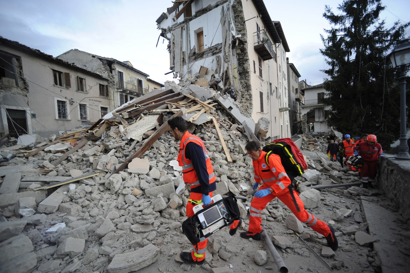Rescuers search a crumbled building in Arcuata del Tronto, central Italy, where a 6.1 earthquake struck just after 3:30 a.m., Wednesday, Aug. 24, 2016. The quake was felt across a broad section of central Italy, including the capital Rome where people  in homes in the historic center felt a long swaying followed by aftershocks. AP Photo/Sandro Perozzi