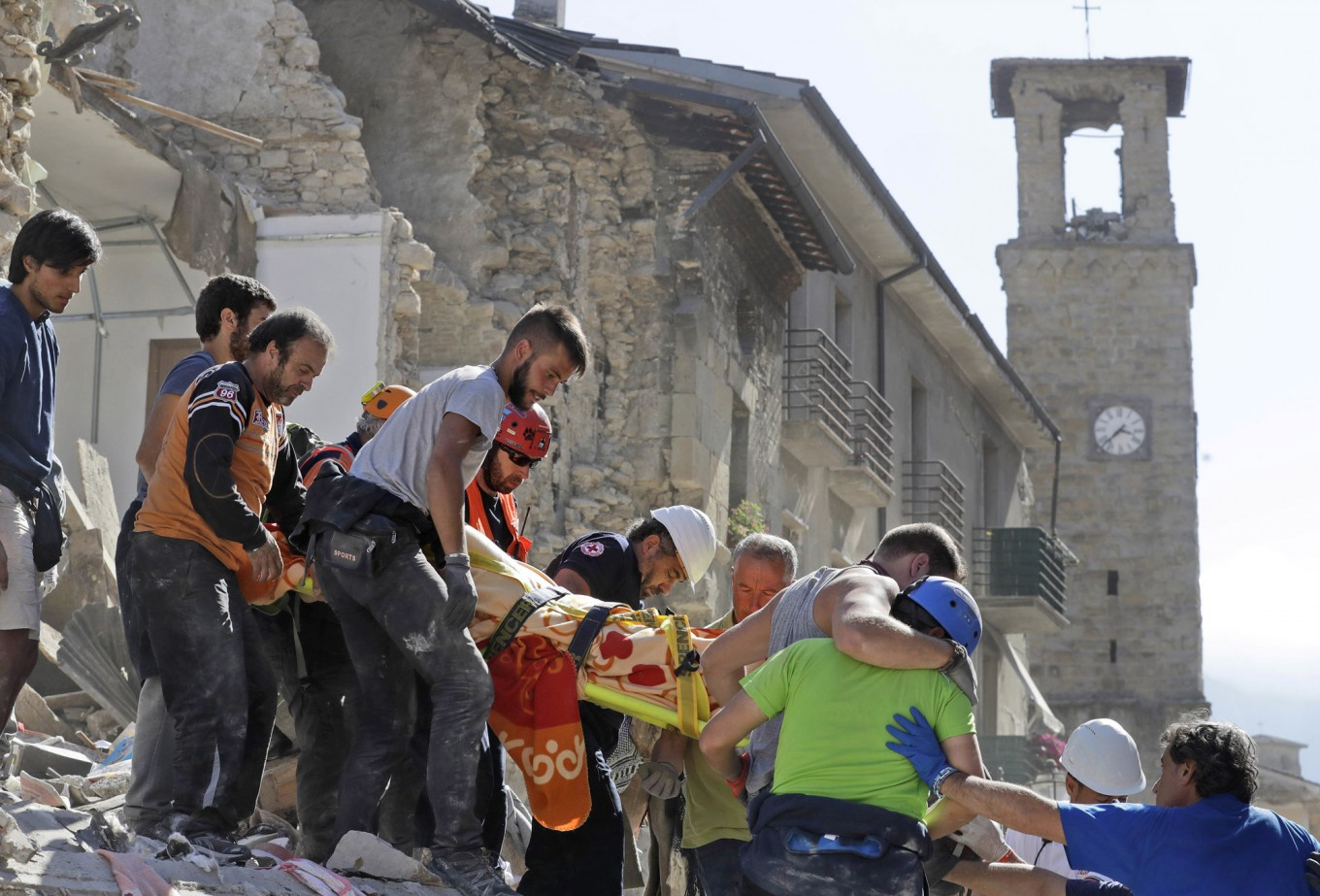 A victim is carried on a stretcher from a collapsed building after an earthquake, in Amatrice, central Italy, Wednesday, Aug. 24, 2016. A devastating earthquake rocked central Italy early Wednesday, collapsing homes on top of residents as they slept. At least 23 people were reported dead in three hard-hit towns where rescue crews raced to dig survivors out of the rubble,  but the toll was expected to rise as crews reached homes in more remote hamlets. AP Photo/Alessandra Tarantino