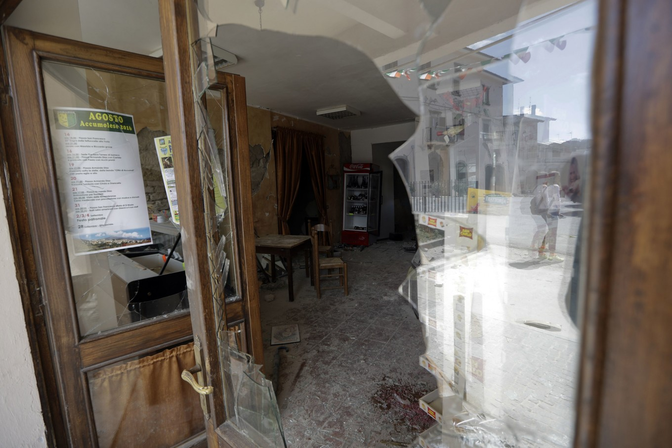Damaged houses are reflected in the shattered window of a cafe, in Accumoli, central Italy, Wednesday, Aug. 24, 2016. The magnitude 6 quake struck at 3:36 a.m. [0136 GMT] and was felt across a broad swath of central Italy, including Rome where  residents of the capital felt a long swaying followed by aftershocks. AP Photo/Andrew Medichini