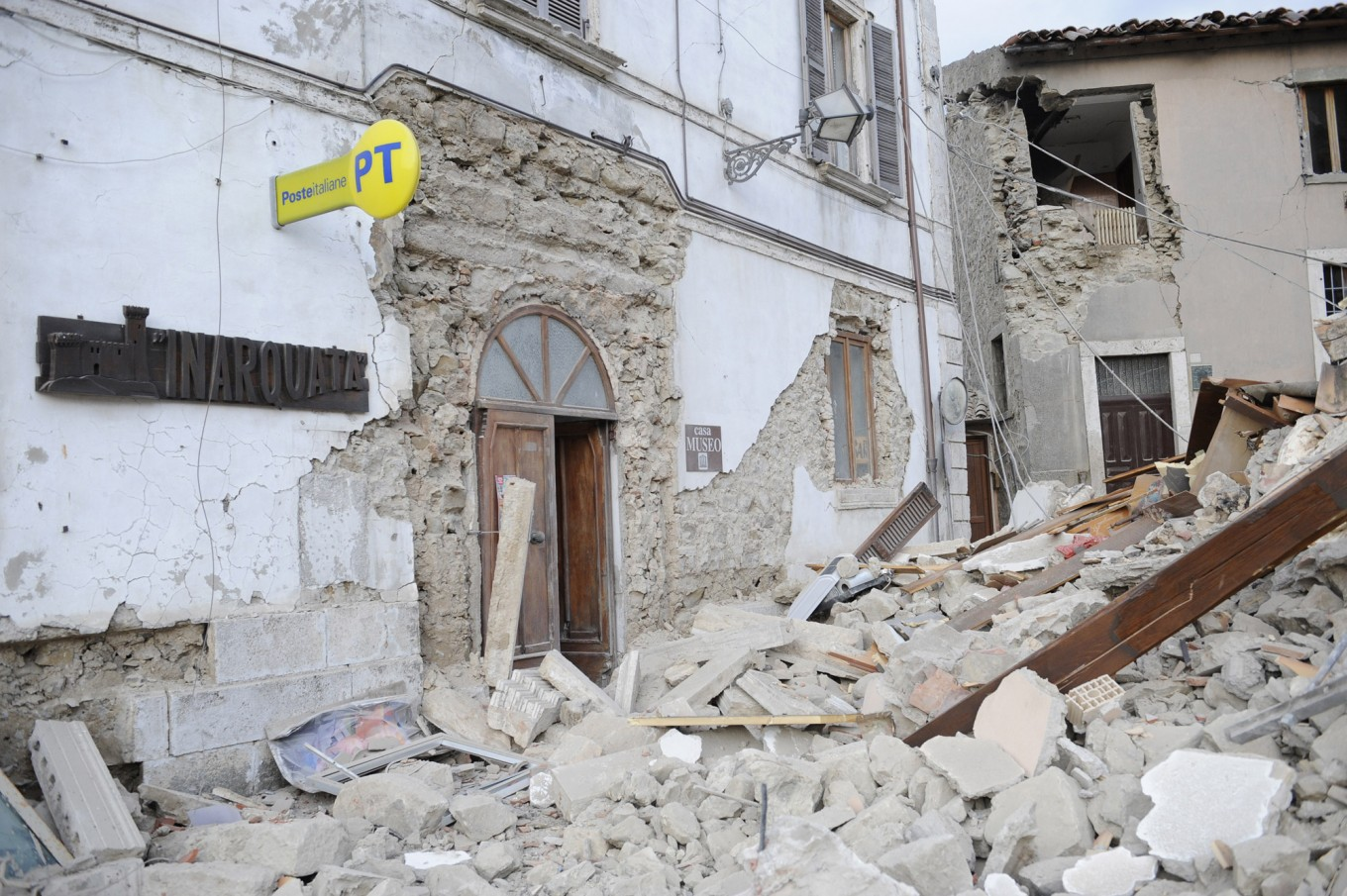 A post office is engulfed by rubbles in Arcuata del Tronto, central Italy, where a 6.1 earthquake struck just after 3:30 a.m., Wednesday, Aug. 24, 2016. The quake was felt across a broad section of central Italy, including the capital Rome where people in homes in the historic center felt a long swaying followed by aftershocks. AP Photo/Sandro Perozzi