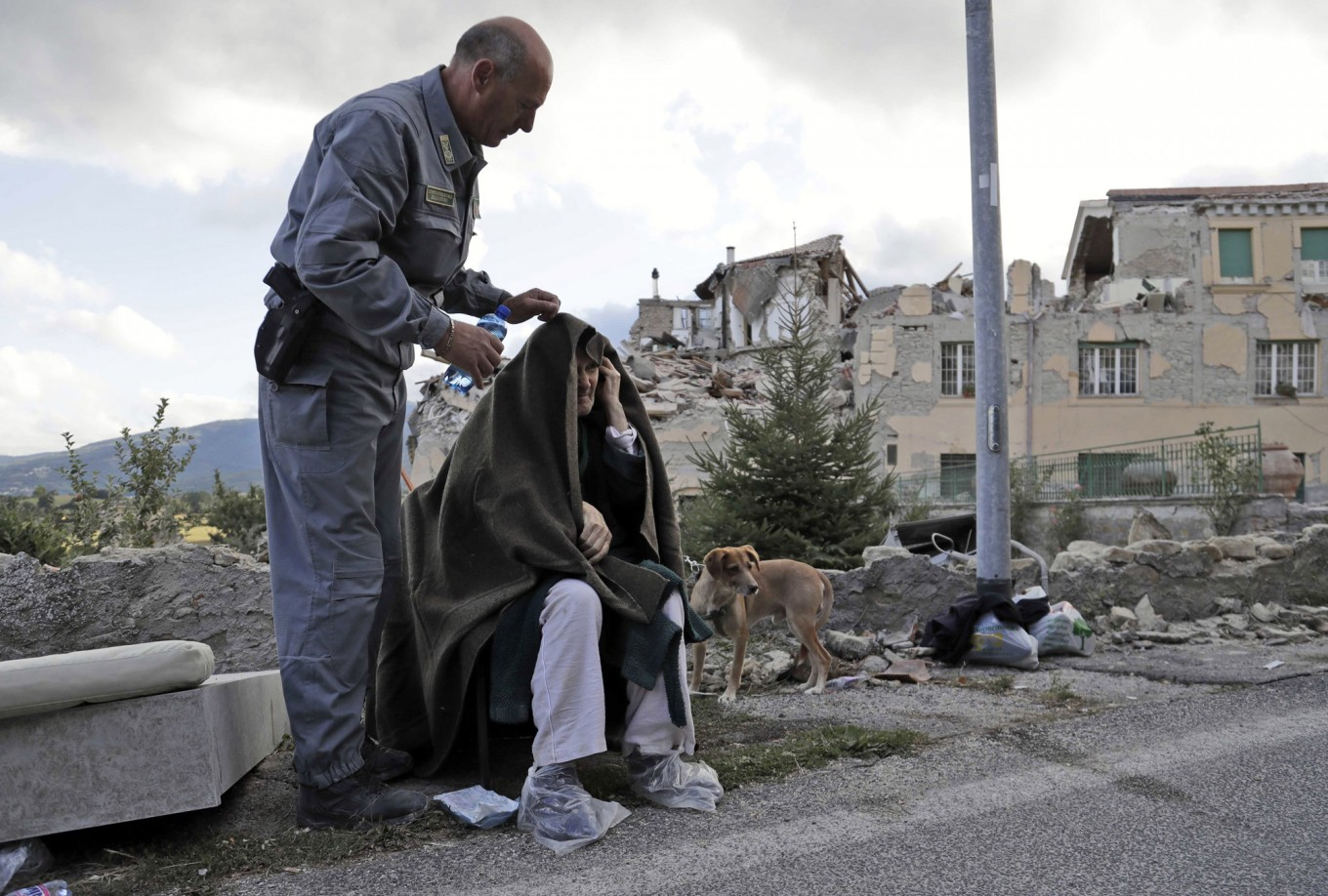 An elderly man is given assistance as collapsed buildings are seen in the background following an earthquake, in Amatrice, Italy, Wednesday, Aug. 24, 2016.  The magnitude 6 quake struck at 3:36 a.m. [0136 GMT] and was felt across a broad swath of central Italy, including Rome where residents of the capital felt a long swaying followed by aftershocks. AP Photo/Alessandra Tarantino