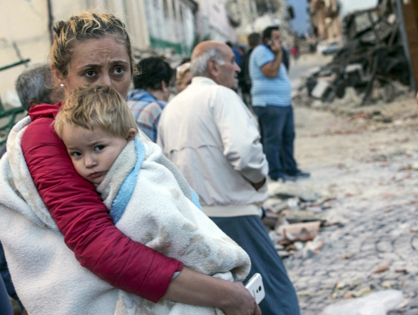 A woman holds a child as they stand in the street following an earthquake, in Amatrice, Italy, Wednesday, Aug. 24, 2016.  The magnitude 6 quake struck at 3:36 a.m. [0136 GMT] and was felt across a broad swath of central Italy, including Rome where residents of the capital felt a long swaying followed by aftershocks. Massimo Percossi/ANSA via AP
