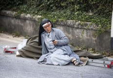 A nun checks her mobile phone as she lies near a victim laid on a ladder following an earthquake in Amatrice Italy, Wednesday, Aug. 24, 2016. The magnitude 6 quake struck at 3:36 a.m. [0136 GMT] and was felt across a broad swath of central Italy, including Rome where residents of the capital felt a long swaying followed by aftershocks. Massimo Percossi/ANSA via AP