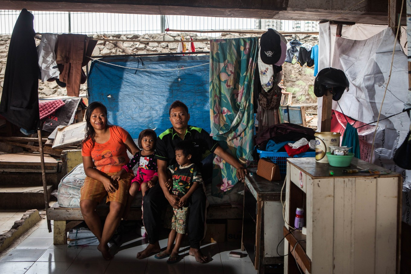 Couple Jony, 29, and Fitri, 24, and their children, Bima, 5, and Kaila, 3, in their home in Pejagalan. They have been living under the toll road since 2008. He worked as a parking attendant before but now he watches and guards trucks that park in the area in exchange for some money. JP/Seto Wardhana