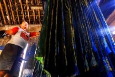 A worker hangs a naturally dyed batik cloth in Bekonang, Sukoharjo, Central Java. JP/Ganug Nugroho Adi.