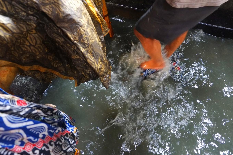 A worker uses his feet to remove wax from a batik cloth in Bekonang, Sukoharjo, Central Java. JP/Ganug Nugroho Adi.