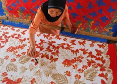 "A batik craftswoman draws batik motifs using a brush, a painting technique referred to as ""colet"". JP/Ganug Nugroho Adi"