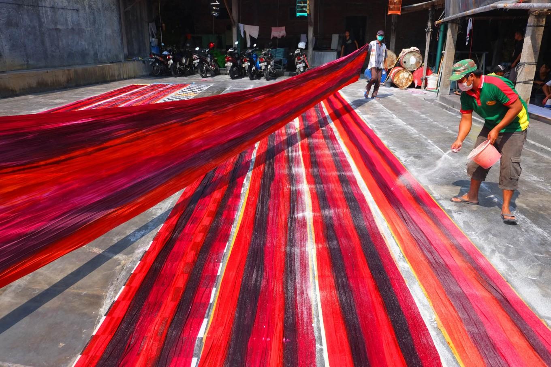 "Workers sprinkle color enhancer on batik cloths drawn using the ""colet"" painting technique. JP/Ganug Nugroho Adi"