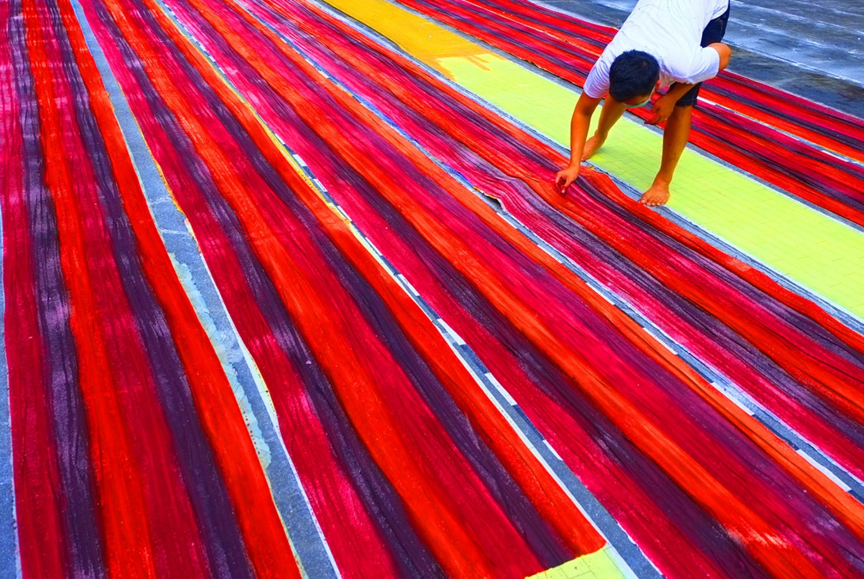 A man checks on a batik cloth after it is painted with colors. JP/Ganug Nugroho Adi