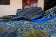A worker folds a batik cloth dyed with natural ingredients. JP/Ganug Nugroho Adi