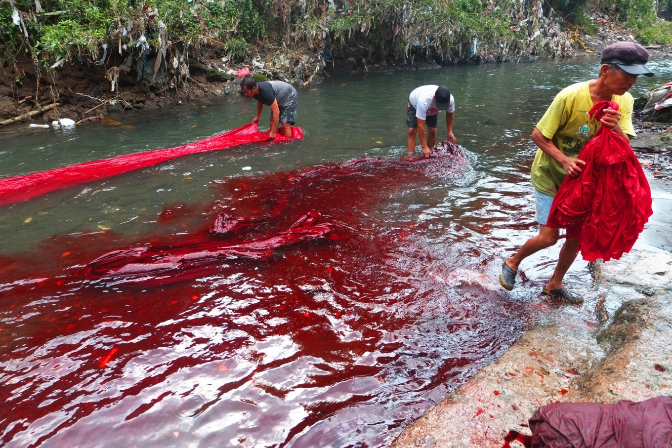Workers wash batik cloths in a river. Waste from naturally dyed batik is less polluting than batik which uses chemical dyes. JP/Ganug Nugroho Adi