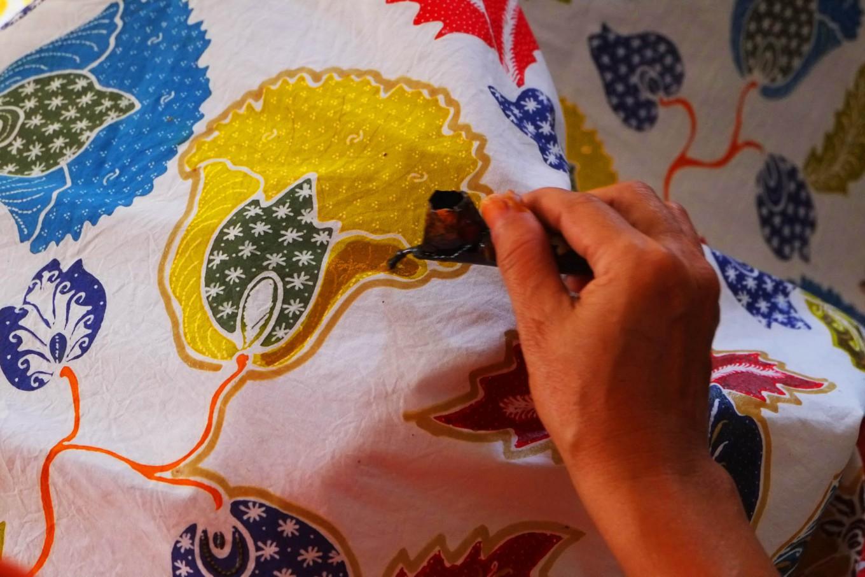 "A batik artisan draws a motif on a cloth using a tool called a ""canting"". JP/Ganug Nugroho Adi."