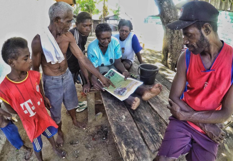 People of the Kamoro tribe read a newspaper in Kampung Lakahia, Kaimana. JP/Wendra Ajistyatama