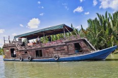 A traditional tongkang boat, once used by illegal loggers, has been converted to accommodate tourists and transport them to Camp Leakey to see the primates.  JP/ Wendra Ajistyatama