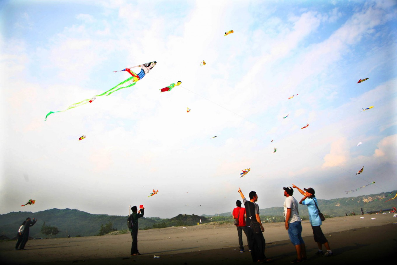 Visitors of the 2016 National Kite Festival observe kites flying in the skies of Parangkusumo Beach in Bantul, Yogyakarta. JP/ Aditya Sagita
